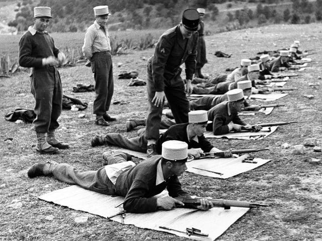 Soldaten mit weissem Käppi liegend in einer Reihe beim Schiessen.