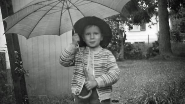 Schwarzweissfoto des Knaben mit Hut und einem grossen Regenschirm.