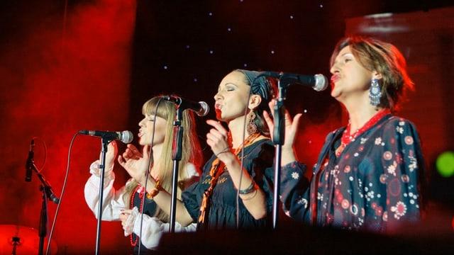Drei Frauen singen in Mikrofone