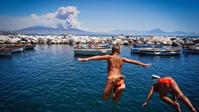 Rauchender Vesuv in der Ferne, im Vordergrund springen zwei Badende Jungs ins Meer.