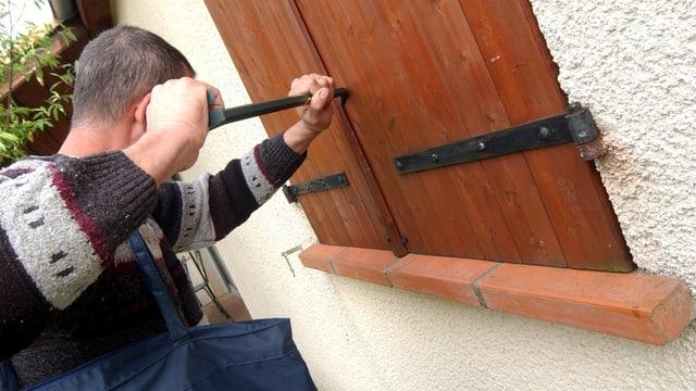 Symbolbild: Junger Mann versucht, einen Fensterladen aus Holz aufzustemmen.