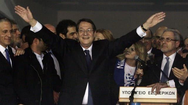 Nikos Anastasiades steht mit ausgebreiteten Armen neben einem Rednerpult (keystone)