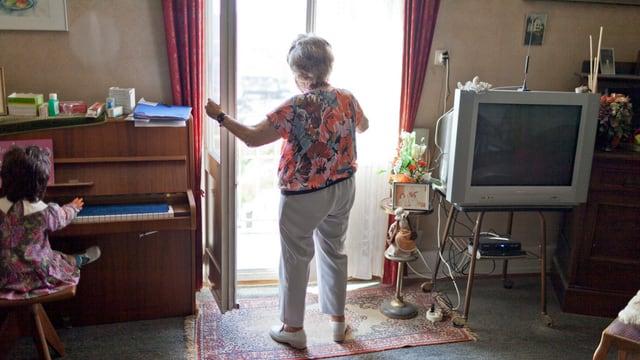 Eine alte Frau, welche in einem Zimmer am Fenster steht.