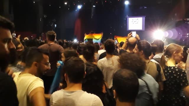 Konzertbesucher in einem Club. Einige halten Regenbogenfahnen hoch.