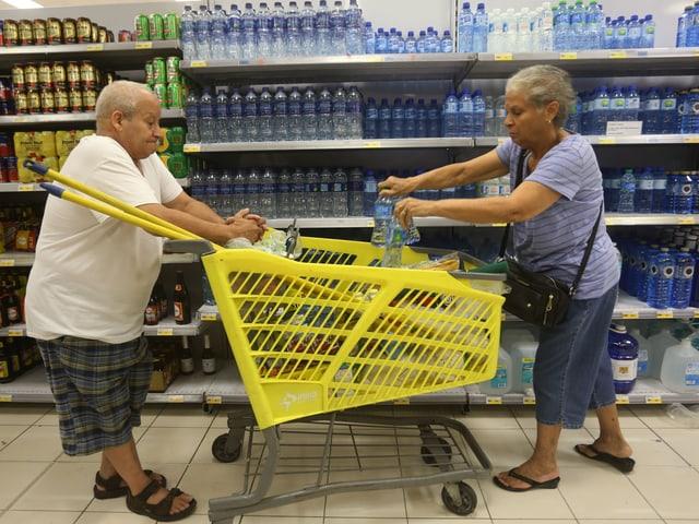 Ein älteres Paar füllen ihren Einkauftswagen mit Wasserflaschen.