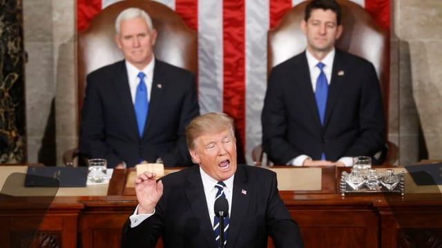 Trump hält eine Rede. Hinter ihm sind Vizepräsident Mike Pence und der Sprecher des Räpresentantenhauses, Paul Ryan.