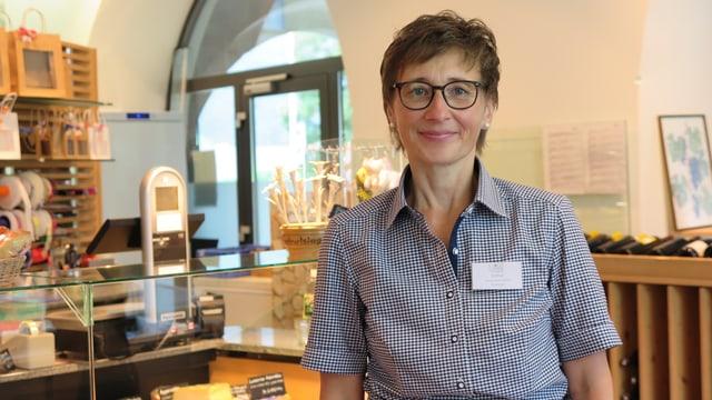 Eine Frau mit kurzem Haar und Brille.