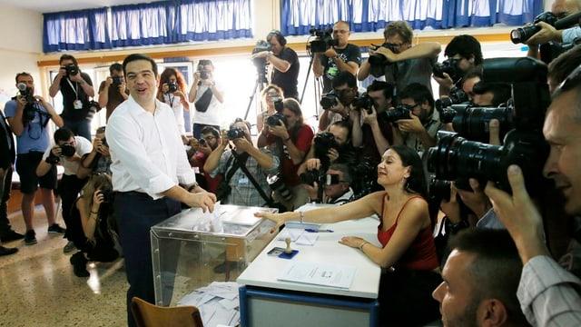 Il primminister grec en in local da votaziun, el metta ses cedel da vuschar en l'urna