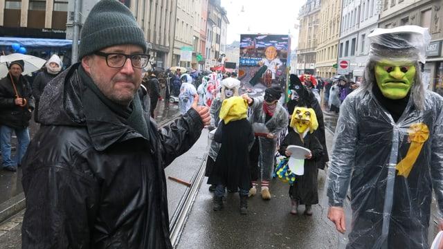 Renatus Zürcher steht mit grüner Wollmütze vor einer kleinen Clique. Auf der Laterne ist Polizeidirektor Baschi Dürr abgebildet.