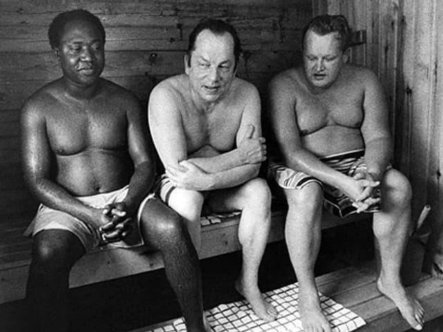 Ahti Karjalainen und Martti Ahtisaari, neben einem afrikanischen Politiker auf der Saunabank sitzend.