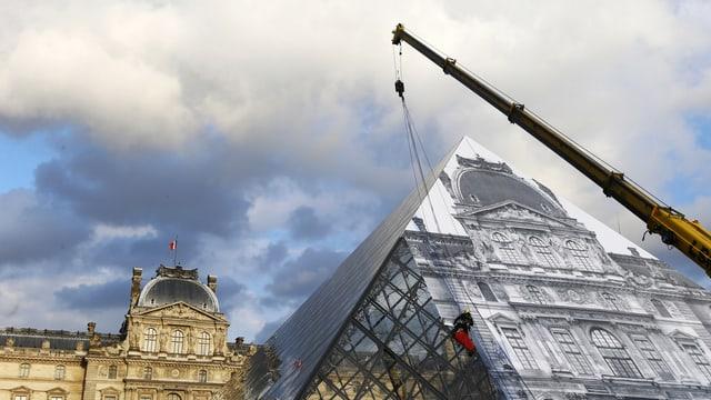Ein Kran steht vor einer Glaspyramide, im Hintergrund ist ein herrschaftliches Gebäude zu erkennen.