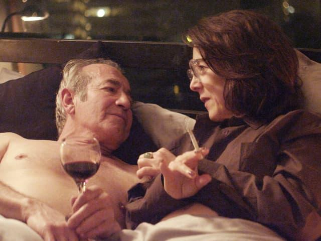 Mann und Frau liegen im Bett. Er hält ein Glas Rotwein, sie raucht.