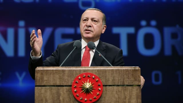 Erdoğan steht am Rednerpult und gestikuliert.