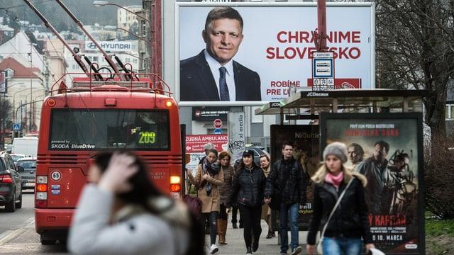 Grosses Werbeplakat vor einer Busstation.