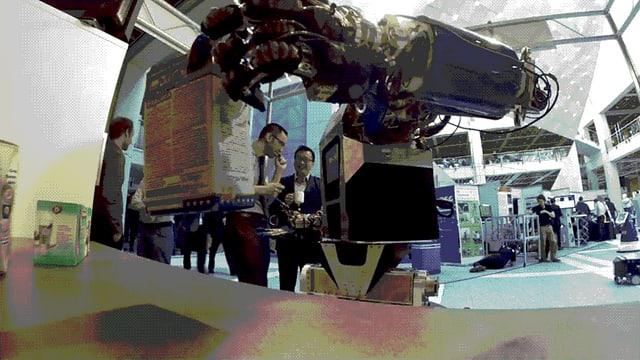 Ein Roboter greift nach einer Schachtel.