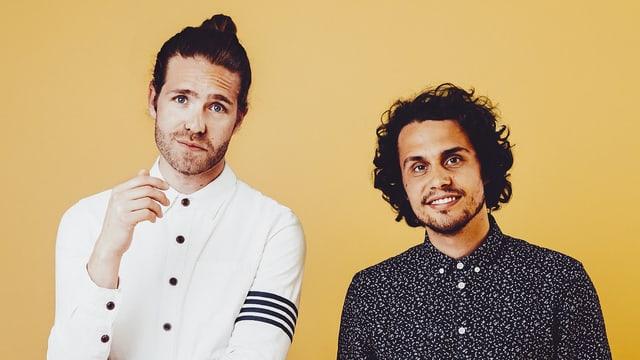 Porträt: Zwei junge Männer stehen lächelnd vor einem gelben Hintergrund.