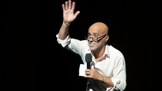 Jürgen Kutter im weissen Hemd mit Brille und Mikro in der Hand im Deutschen Theater Berlin.
