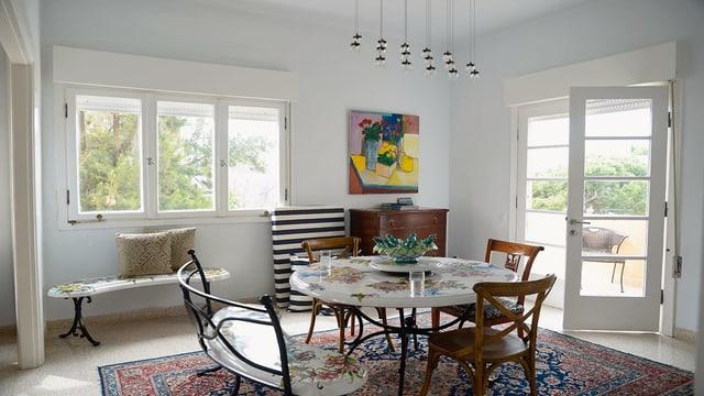 Blick in ein helles Wohnzimmer. In der Mitte ein runder Tisch mit Holzstühlen.