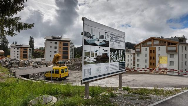 Baustelle eines Mehrfamilienhauses mit Informationstafel
