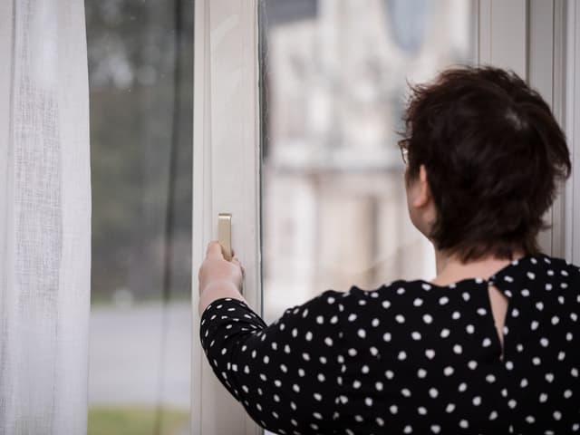 Eine Frau von hinten, die ein Bürofenster öffnet und in Kipplage bringt.