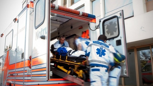 Vier Sanitäter in weiss-blauen Kleidern schieben einen Patienen auf einer Bare in einen Ambulanz-Wagen.