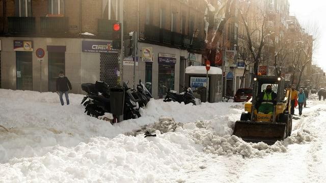 Ein Fahrzeug räumt Schnee auf einer Madrider Strasse weg.