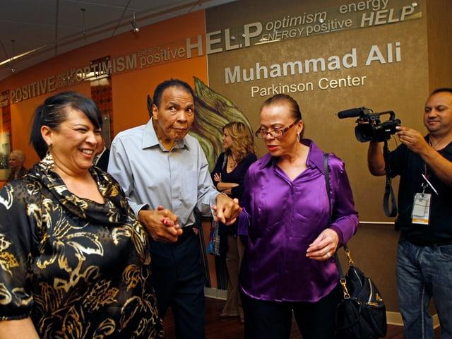Ali  von Parkinson gekennzeichnet im Jahr 2012 bei einem öffentlichen Auftritt wird gestützt von seiner Frau und seiner Schwägerin