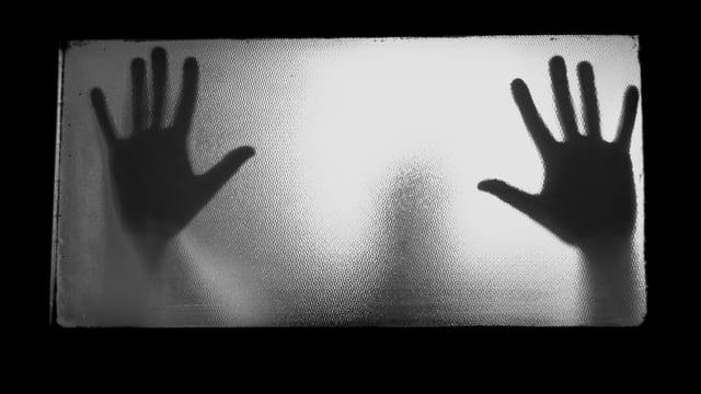 Hände an einer Türscheibe.