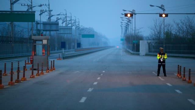 Polizist auf einer einsamen Strassenkreuzung im Industriekomplex Kaesong, Nordkorea.