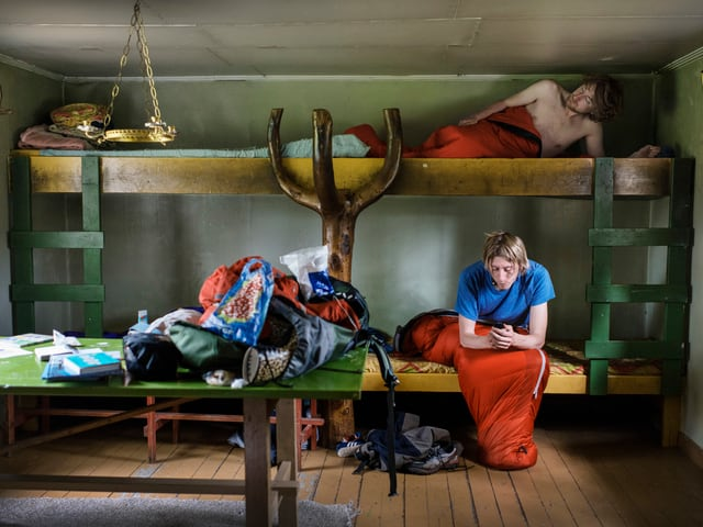 Ein Mann und eine Frau in einem Hochbett in einer schwedischen Ferienhütte.