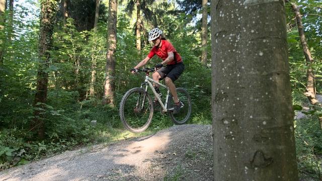 Eine Mountainbikerin fährt einen Veloweg im Wald herunter