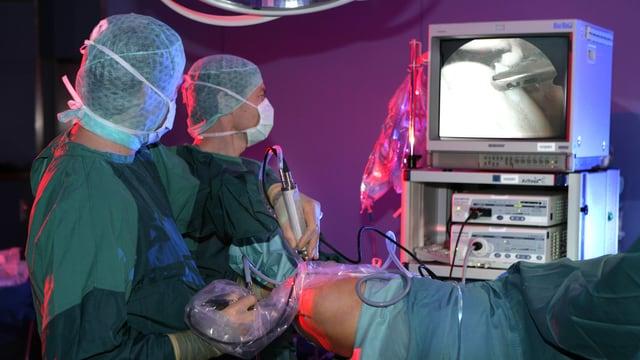 Zwei Chirurgen operieren ein Knie mittels Arthroskopie.