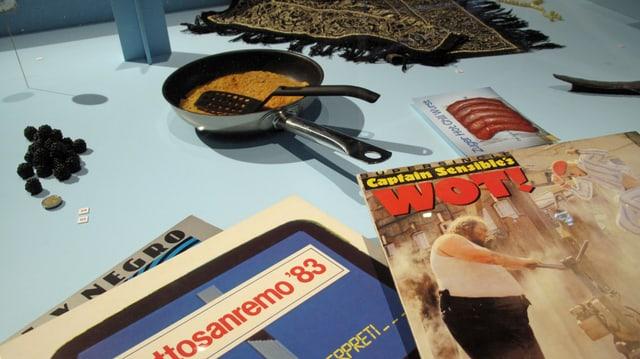 Stilleben mit einer Pfanne mit Rösti drin, einem Reisekatalog und einer Zeitschrift.