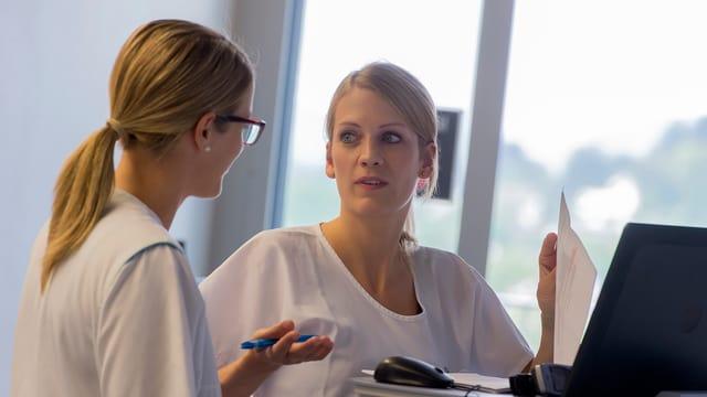 Zwei Frauen im Spital diskutieren miteinander.