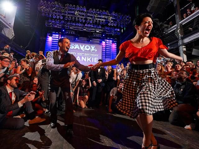 Ein tanzendes Paar. Die Zuschauer bilden einen Kreis um das Paar.