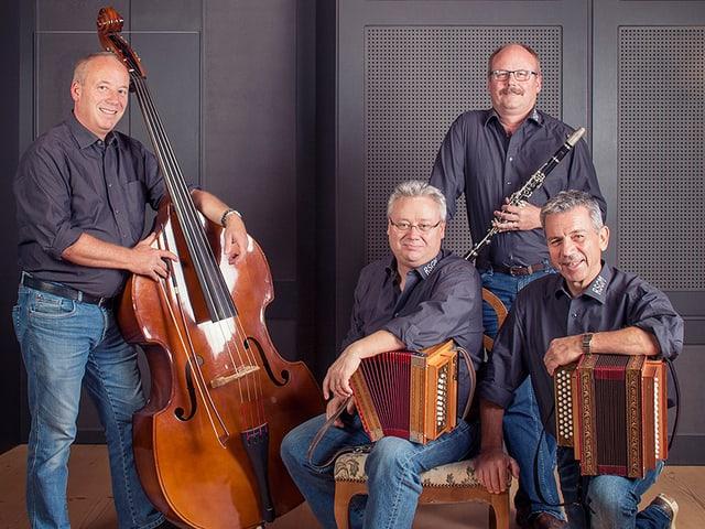 Vier Musikanten mit ihren Instrumenten: Kontrabass, Schwyzerörgeli und Klarinette.