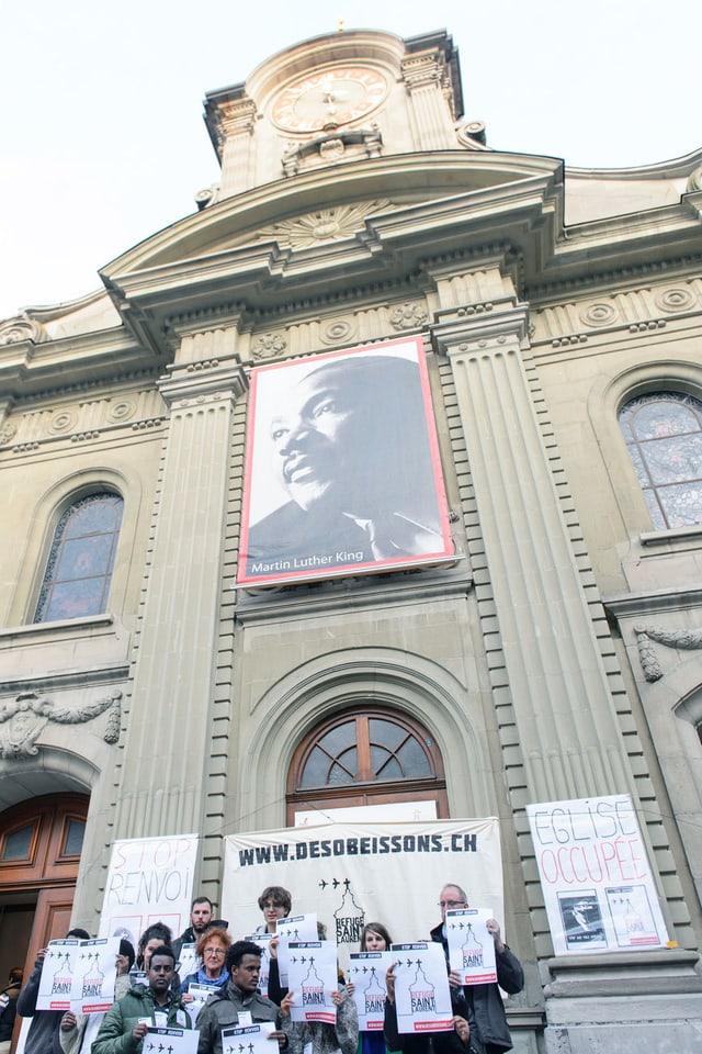 Menschengruppe mit Plakaten steht vor Kirche.