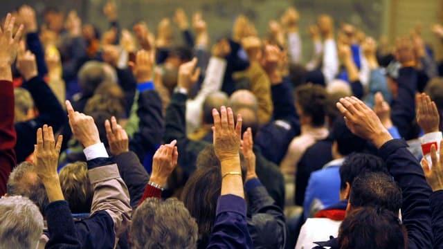Hände in einer Abstimmung einer Gemeindeversammlung