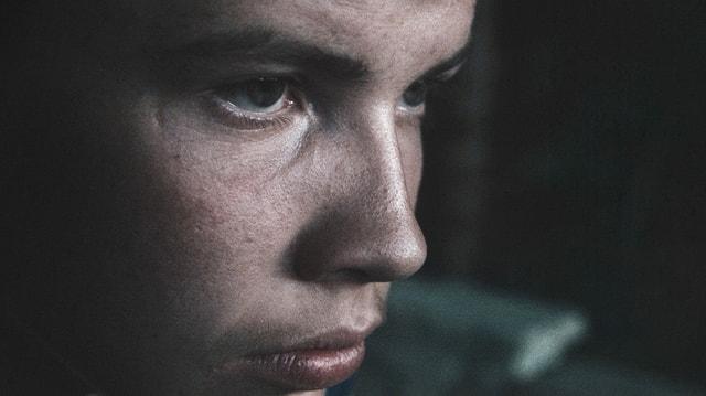Ein Junge schaut durch einen Spalt.