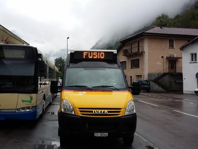 Ein Kleinbus in den Farben des Postautos steht am Bahnhof bei Regenwetter.