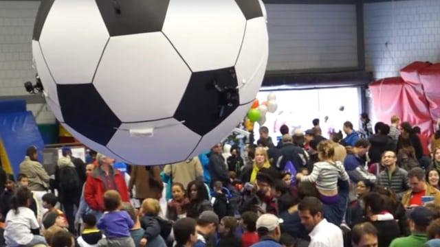 Ballon in Form eines Fussballes schwebt über einer Menschenmenge.