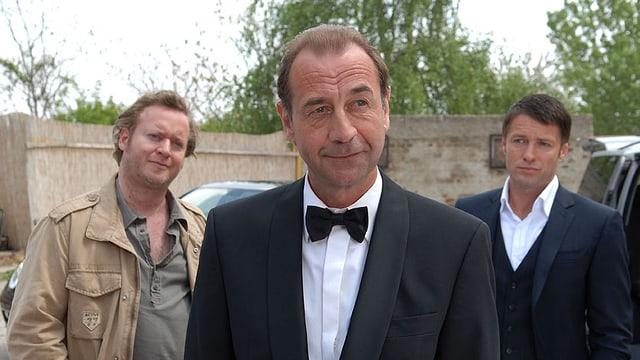 Es sind drei Männer zu sehen, dar Mann in der Mitte trägt einen Anzug mit weissem Hemd und Fliege.
