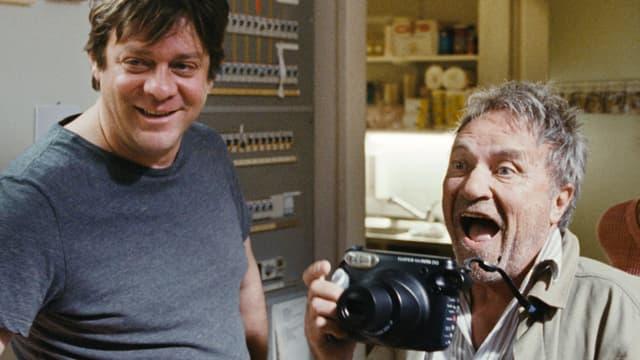 Ein Mann macht ein Foto und verzieht das Gesicht. Ein anderer Mann steht daneben.