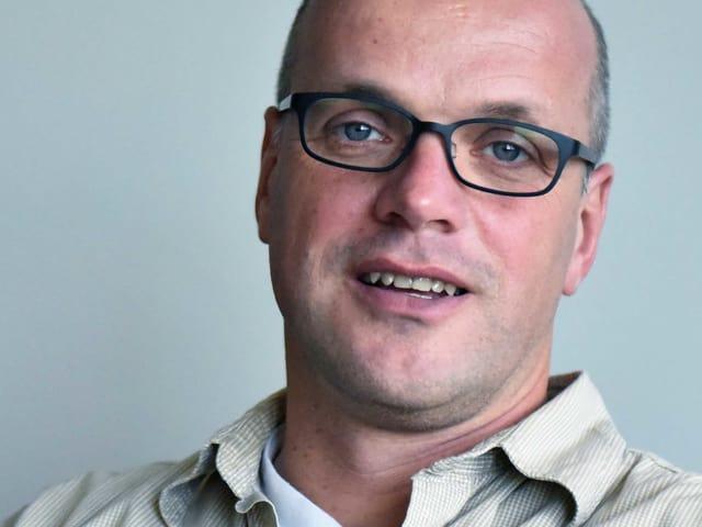 Ein Porträt eines Mannes. Er trägt eine Brille.