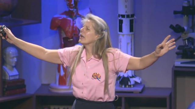 Eine Frau mit blonden Haaren hält die Arme in die Luft, während sie vor Leuten spricht.
