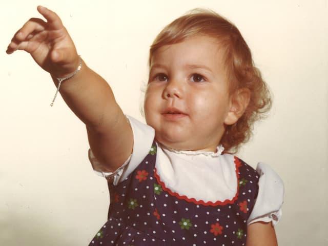 Kleines Mädchen mit ausgestrecktem Zeigefinger.