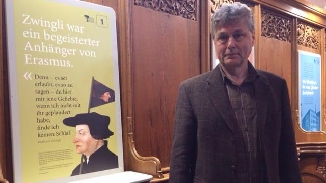 Mann neben Bildtafel in Kirche