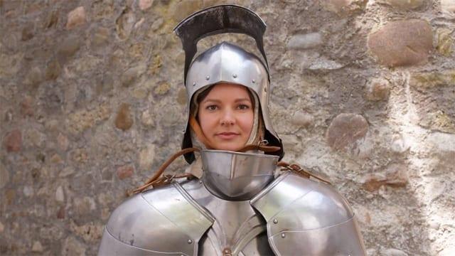Moderatorin Monika Erni trägt eine Ritterrüstung und steht vor einer steinernen Wand.
