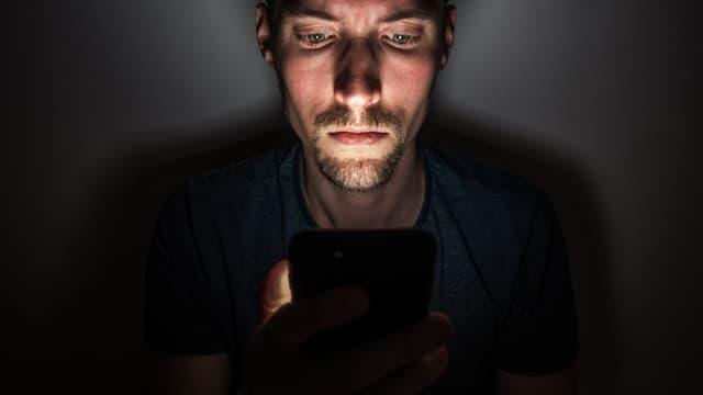 Ein Mann schaut auf ein Handy.