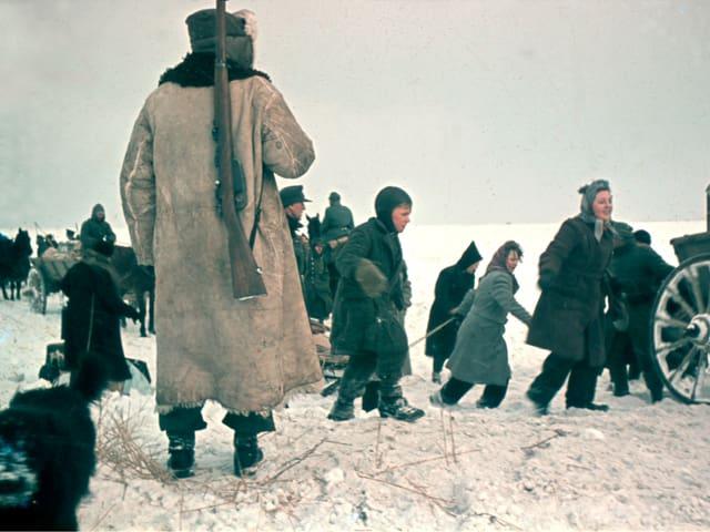 Menschen im Schnee. Sie tragen warme Kleider. Sie sind auf der Flucht.